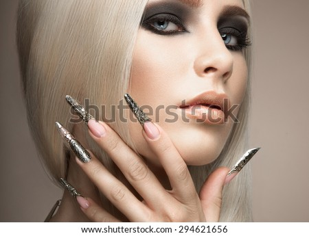 Beautiful fashionable girl in a glamorous image with bright makeup and long silver nails. Art design manicure. Picture taken in the studio. - stock photo