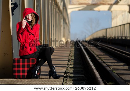 Beautiful fashionable girl waiting for the train on sunny windy day.