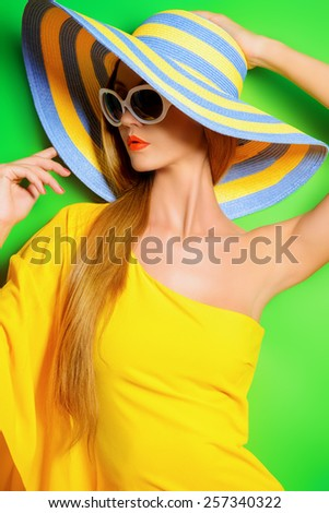 Beautiful fashionable lady wearing bright yellow dress over green background. Beauty, fashion concept. Optics. Summer vacation. - stock photo