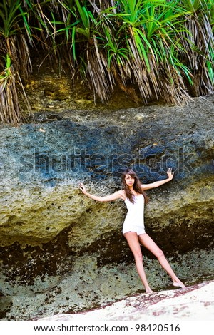 Beautiful fashionable model on the beach standing near rock - stock photo