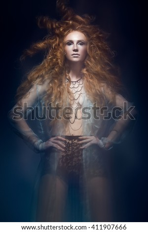 Beautiful fashionable red-haired girl in a transparent dress in mermaid image with creative hairstyle curls. Fashion beauty style. Photos shot in a studio with a mixed light - stock photo