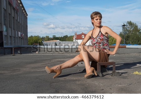 Beautiful fashionable sexy girl in high heels having fun on a skateboard on the roof. On the background of an abandoned factory.