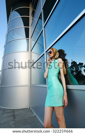 Beautiful fashionable urban girl standing in front of modern office building made of glass and metal.