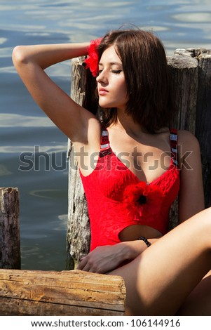 Beautiful fashionable woman getting a tan near the water