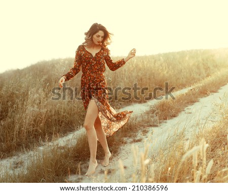 Beautiful fashionable woman in a dress in the sun in the wind walks in a field on the way - stock photo