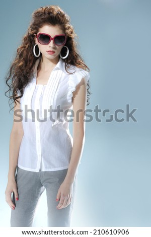 Beautiful fashionable woman in sunglasses posing on light background - stock photo