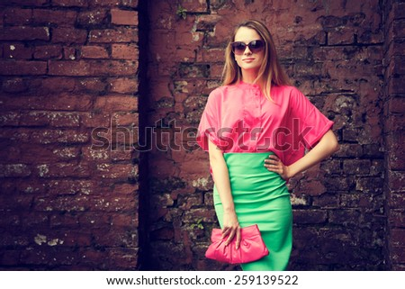 Beautiful Fashionable Woman Standing at the Old Brick Wall Background. Urban Fashion Concept. Toned Photo with Copy Space. - stock photo