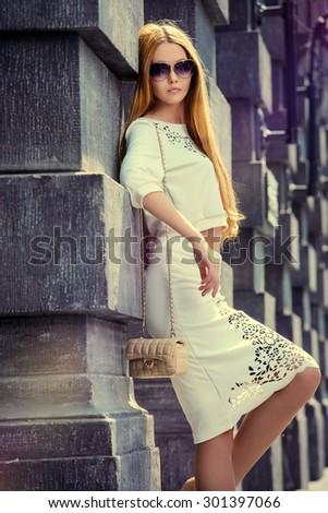 Beautiful fashionable woman standing on the city street. Elegant businesswoman outdoor.  - stock photo