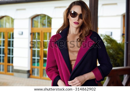 Beautiful fashionable young business woman wearing in autumn coat and sunglasses with hairdo and makeup walking on a street with fall near big house and trees without yellow leaves background - stock photo