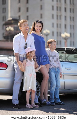 Beautiful father, mother and two children stand near convertible car; man laughs - stock photo