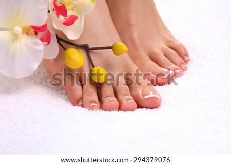 Beautiful feet with perfect spa french nail pedicure - stock photo