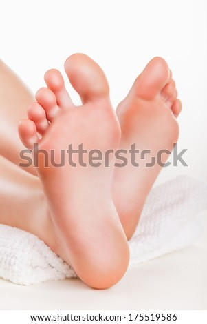 Beautiful female a foot and a heel on a white background