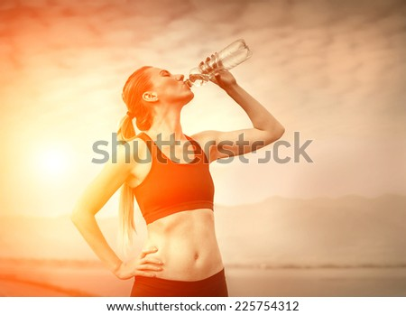 Beautiful female after running, drink water under sky - stock photo