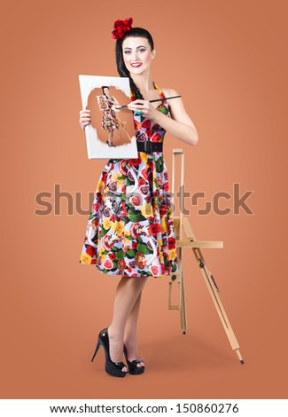 Beautiful female artist painting a self portrait with oil paint brush and canvas in hand with easel background. Art tutorial and leaning concept - stock photo