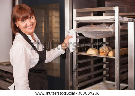 Beautiful female baker is cleaning the equipment after baking. The woman is smiling and looking at the camera with joy. She is holding cloth in her left hand - stock photo