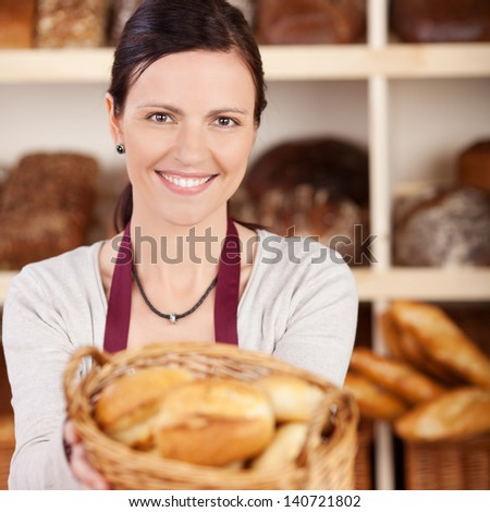 Beautiful female bakery worker with a charming friendly smile offering a basket of assorted bread to the viewer - stock photo