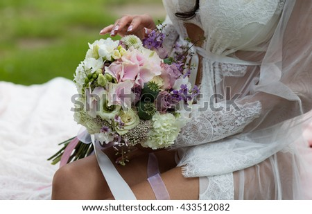 Beautiful female bare feet in the bridal negligee. Bride putting a wedding bouquet on his feet - stock photo