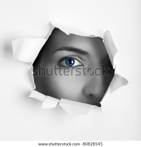 Beautiful female blue eye looking through a hole on a sheet of paper - stock photo
