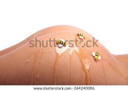 Beautiful female body in honey on white background, studio - stock photo