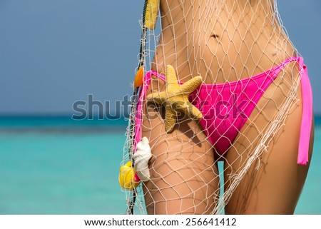 Beautiful female body on the beach, conceptual image of vacation, spa, travel and summertime holidays  - stock photo