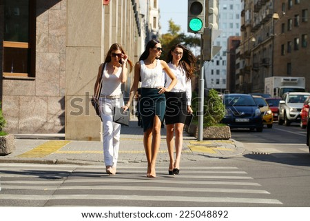 Beautiful Female business team marching down the street in the summer