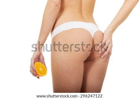 Beautiful female buttocks with an orange.