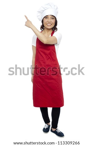 Beautiful female chef pointing at the copy space. Full length shot