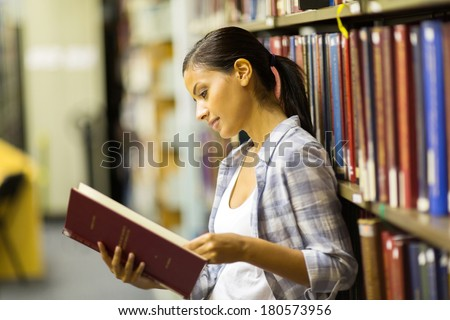 beautiful female college student reading a book in library