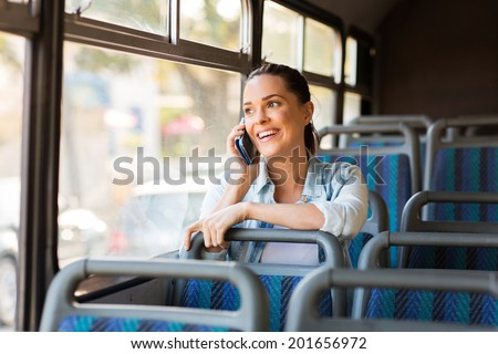 beautiful female commuter talking on cell phone while taking bus to work - stock photo