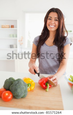 Beautiful female cooking vegetables while standing in the kitchen