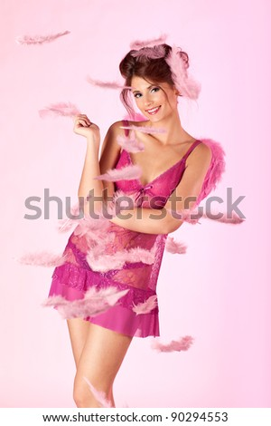 Beautiful female cupid in a rain of feathers on pink background. - stock photo