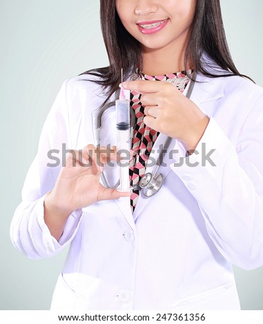 beautiful female doctor carrying a syringe, isolated on green background - stock photo