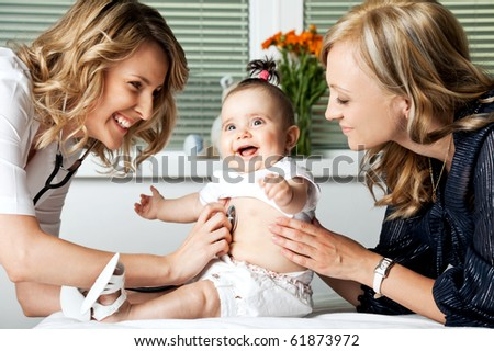 Beautiful female doctor examining little smiling baby girl, held by mother - stock photo