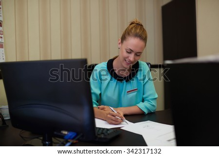 Beautiful female entrepreneur with a busy schedule working in her office while signing documents, young attractive and successful businesswoman sitting at the table with pc computer doing paperwork