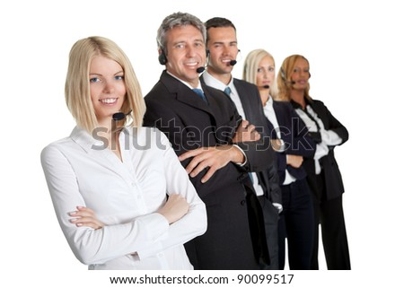 Beautiful female executive wearing headset with colleagues in background - stock photo