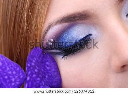 Beautiful female eye with bright blue make-up and orchid flower