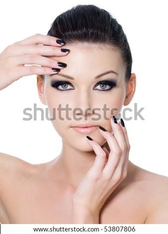 Beautiful  female face with black eye make-up and black manicure - stock photo