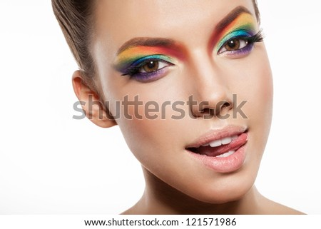 beautiful female face with rainbow makeup. girl showing tongue - stock photo