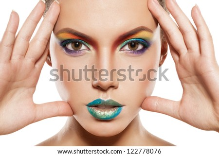 beautiful female face with rainbow makeup. girl touch her face by hands - stock photo