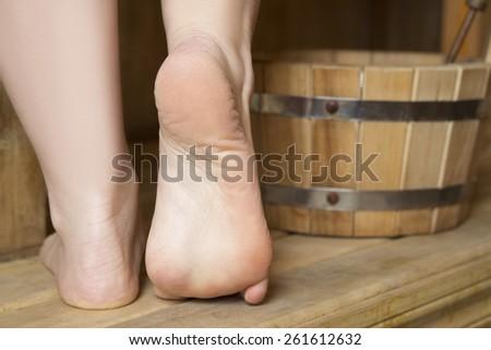 Beautiful female feet in sauna, bath accessories. Wooden bucket - stock photo