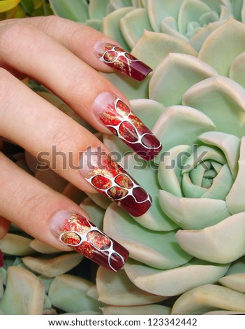 Beautiful female fingers with nice abstract foil nail art design manicure on an exotic flower - stock photo