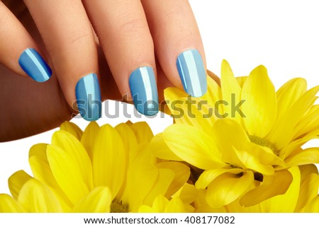 Beautiful female fingers with trend blue manicure touching spring flowers. Care about female hands, healthy soft skin. Spa & cosmetics. Close-up of beautiful fingers with nails polish  - stock photo