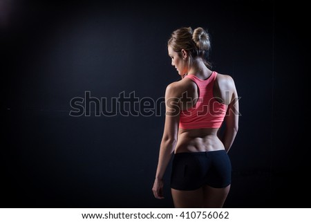 Beautiful female fitness model holding her towel/weights in a dark studio while covered in sweat after her training. - stock photo