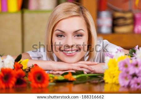 Beautiful female florist. Beautiful young blond hair woman leaning at the table full of flowers and smiling - stock photo