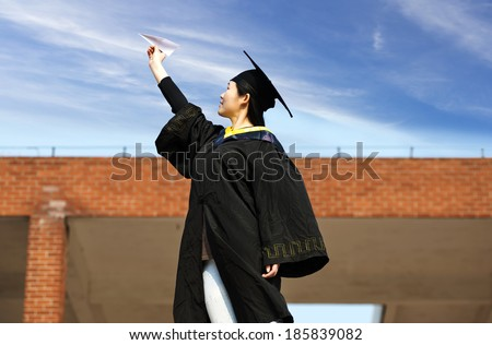 Beautiful female graduate wearing a graduation gown, throwing airplane - stock photo