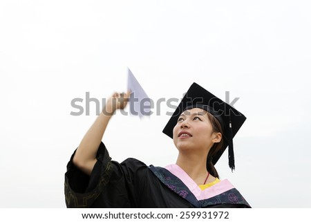 Beautiful female graduates wearing a graduation gown,throwing paper-plane - stock photo