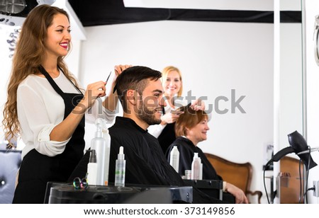Beautiful female hairdresser is making a modern haircut for a male customer