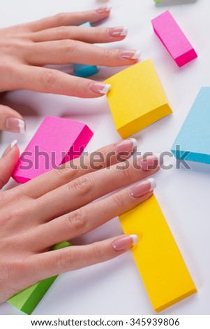 Beautiful female hand on a background of multicolored abstraction. French manicure on a bright background. - stock photo