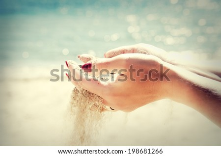 Beautiful female hands and the sand on the sea background - stock photo