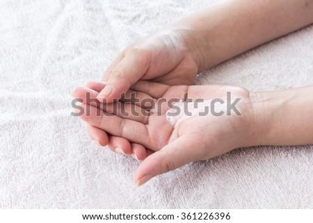 Beautiful female hands applying hand cream - stock photo